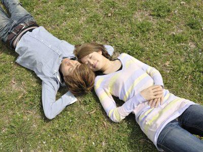 芝生に寝転がる友達以上恋人未満の男女