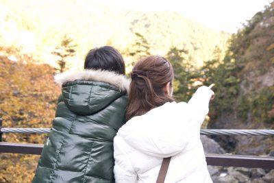 吊り橋から景色を見るカップル