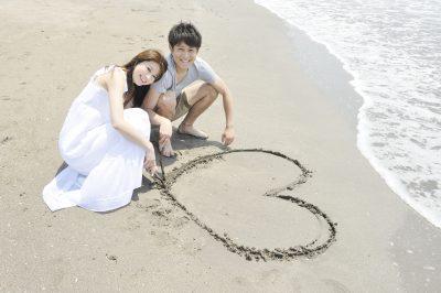 砂浜にハートを描く若いカップル