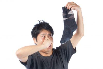 臭い靴下を持つ不潔な男性