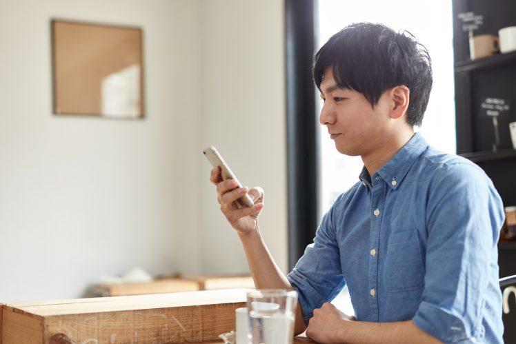 カフェでOmiaiアプリを使う男性イメージ