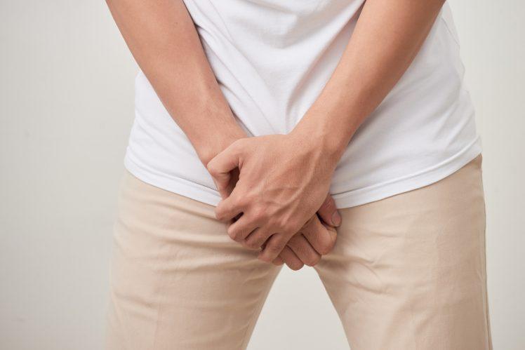 股間を抑える早漏の男性