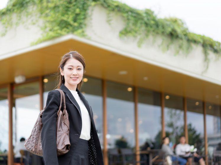 カフェの前に立つOL女性