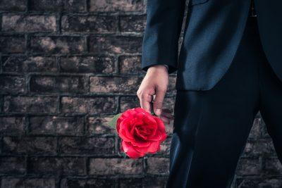 バラの花を持っている遊び慣れた男性