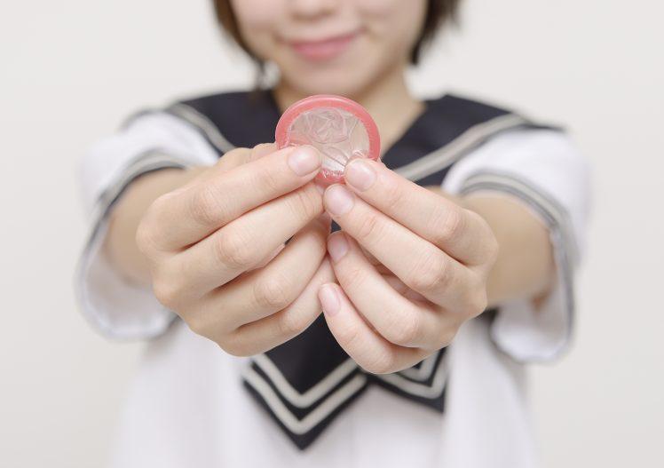 コンドームを持つ女子高校生