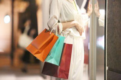 店のショッパーを持つ女性