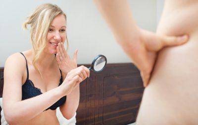 拡大鏡でペニスを見る女性
