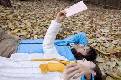 枯れ葉の上で添寝をする男女
