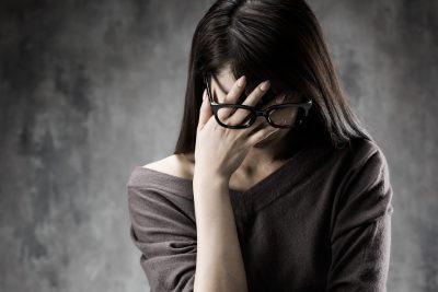 年齢の壁に悩み顔を覆う女性