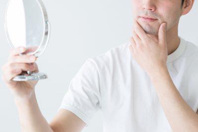 髭の剃り残しを鏡でチェックする男