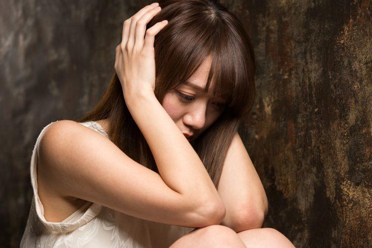 不安を感じ頭を抱える風俗嬢 イメージ