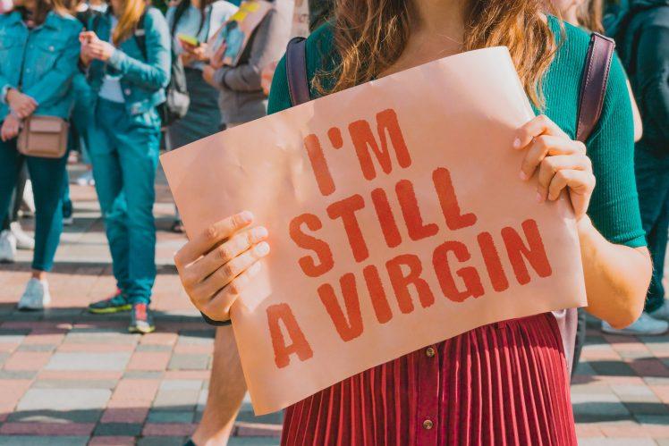 「まだ処女」というプラカードを持つ女性