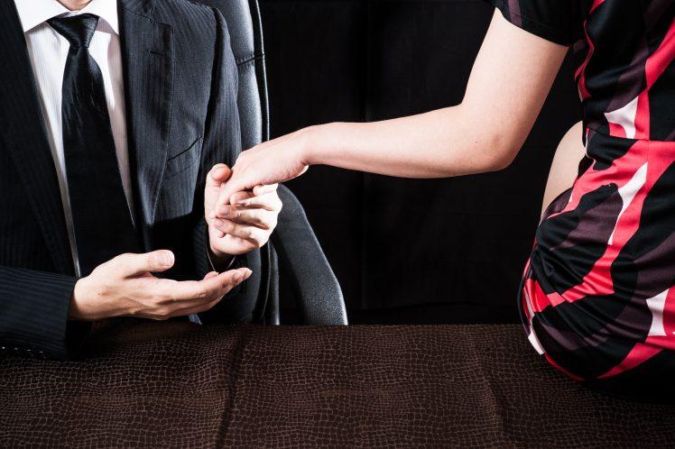 会社で手を握っている不倫カップル